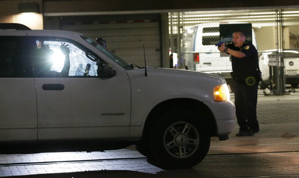 Dallas police stop a driver in downtown Dallas, Thursday, July 7, 2016, following shootings of police officers. Snipers apparently shot police officers during protests and some of the officers are dead, the city's police chief said in a statement.