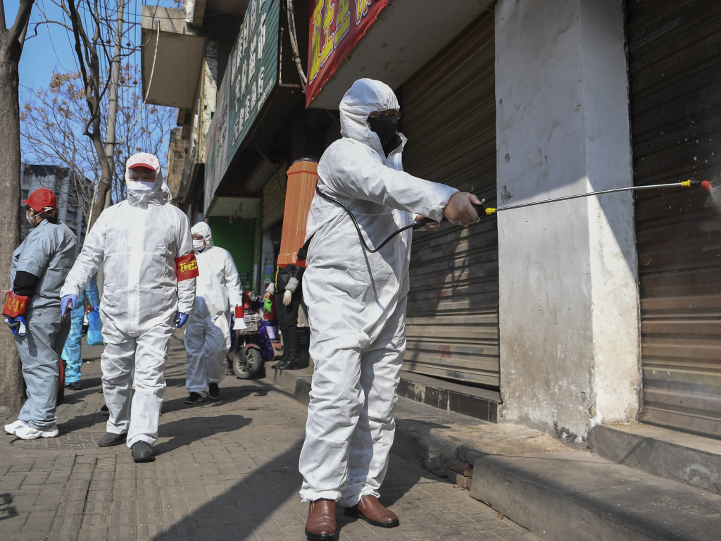 In a photo released by the Xinhua News Agency, workers disinfect closed shop lots following the coronavirus outbreak, in Jiang'an District of Wuhan in central China's Hubei Province, on Monday.