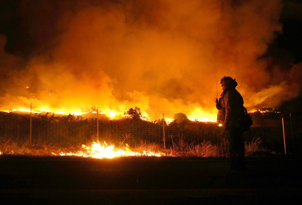 A firefighter monitors the Kincaide Fire as it burns through the area on October 24, 2019 in Geyserville, California.