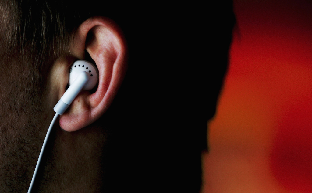 A man listens to an iPod MP3 player through earphones August 17, 2005 in Sydney, Australia.