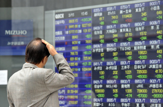 A pedestrian gazes at a share prices board in Tokyo on March 15, 2011.