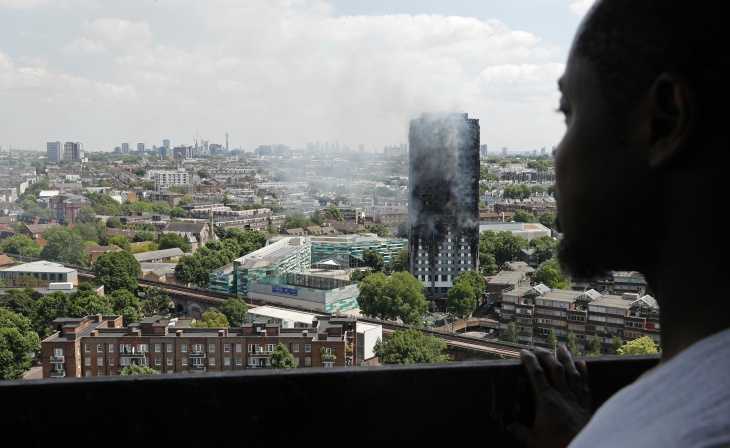 Smoke and flames billows from Grenfell Tower as firefighters attempt to control a blaze at a residential block of flats on June 14, 2017 in west London. At least six people were killed Wednesday when a massive fire tore through a London apartment block in the middle of the night, with witnesses reporting terrified people had leapt from the 24-storey tower. / AFP PHOTO / Adrian DENNIS        (Photo credit should read ADRIAN DENNIS/AFP/Getty Images)