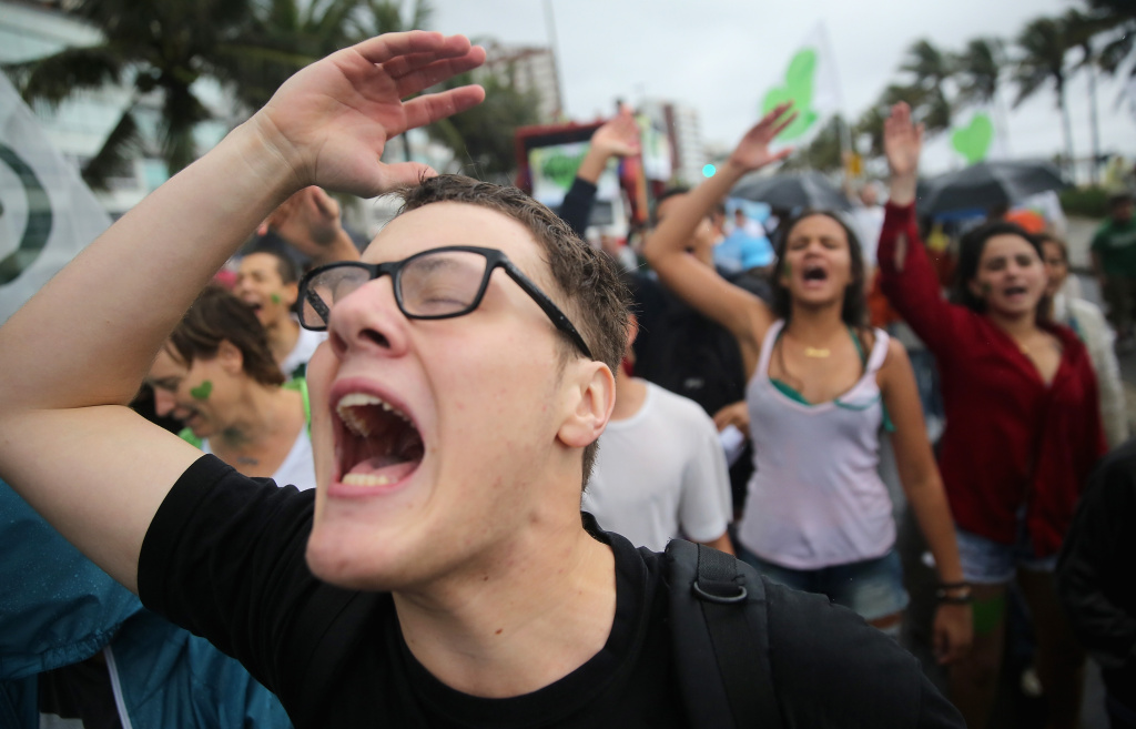 Participants chant and sing during the climate march along Ipanema beach on September 21, 2014 in Rio de Janeiro, Brazil. Protests calling for curbs in greenhouse gas emissions were scheduled for today in 150 countries ahead a U.N. summit on climate change. The Amazon rainforest, mostly located in Brazil, produces about 20 percent of the earth's oxygen but is threatened by deforestation.