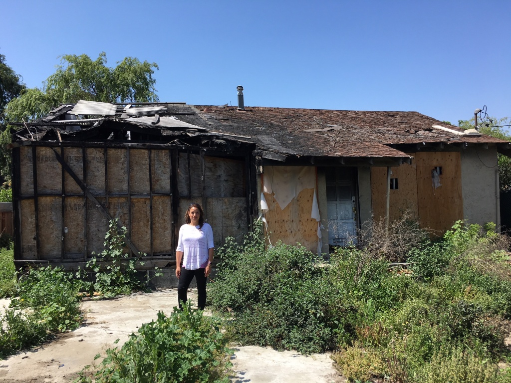 Real estate agent Holly Barr stands outside the burned out San Jose house she sold for more than $900,000.