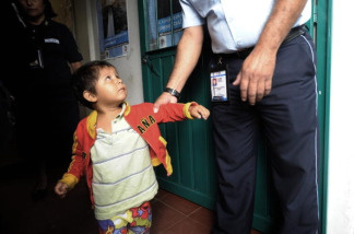 An immigration officer holds a child by his arm.