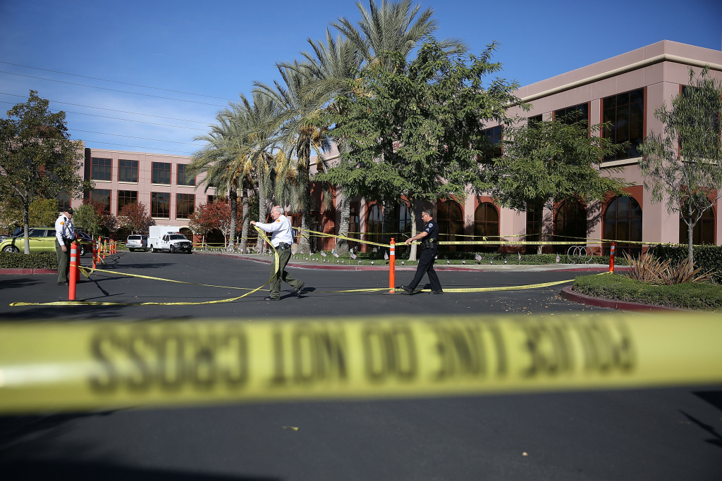 Officials put up police tape in front of the building at the Inland Regional Center were 14 people were killed on Dec. 7, 2015 in San Bernardino.
