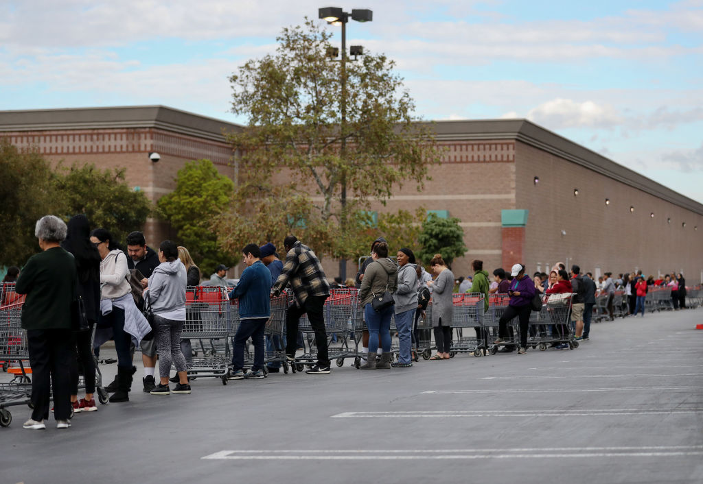 People wait in line to enter a Costco Wholesale store before it opened in the morning on March 12, 2020 in Glendale, California.
