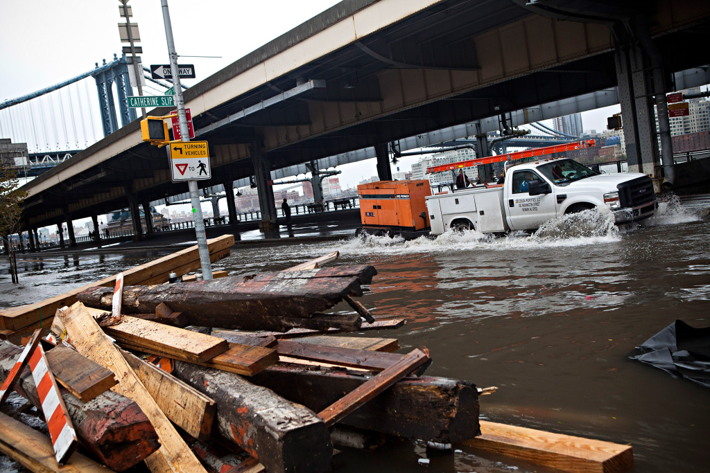 A truck drives through a flooded street, caused by Hurricane Sandy, on October 30, 2012, in the Lower East Side of New York City. The storm has claimed at least 16 lives in the United States, and has caused massive flooding accross much of the Atlantic seaboard. US President Barack Obama has declared the situation a 'major disaster' for large areas of the US East Coast including New York City.