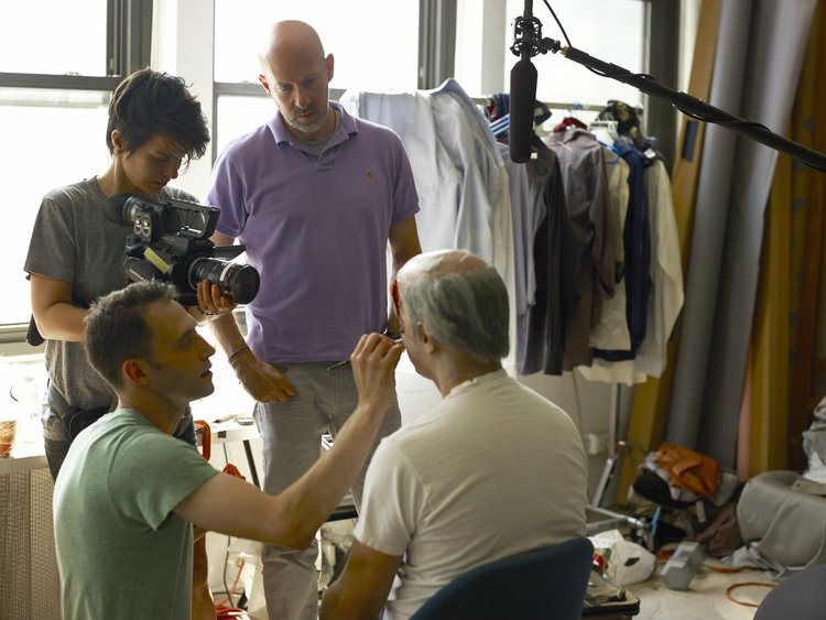Filmmaker Joshua Seftel (purple shirt) interviews artist Phil Toledano (in make-up chair) on the set of