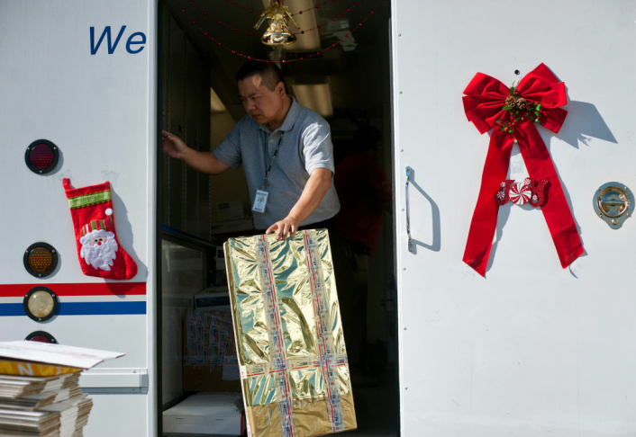USPS Retail Specialist Phillip Chan gathers gifts that are ready to be mailed as part of Operation Santa on Thursday, Dec. 20. Letters addressed to Santa stay in the area where they were mailed. Volunteers can come in at any time to