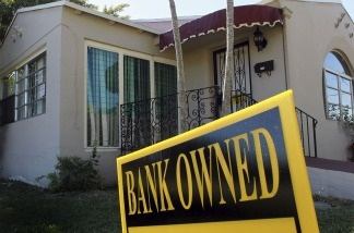A bank owned sign is seen in front of a foreclosed home on December 7, 2010 in Miami, Florida. Foreclosure sales made up 39.7 percent of home sales in Miami-Dade, Broward and Palm Beach counties, up from 34.02 percent the previous quarter, according to a recent report.