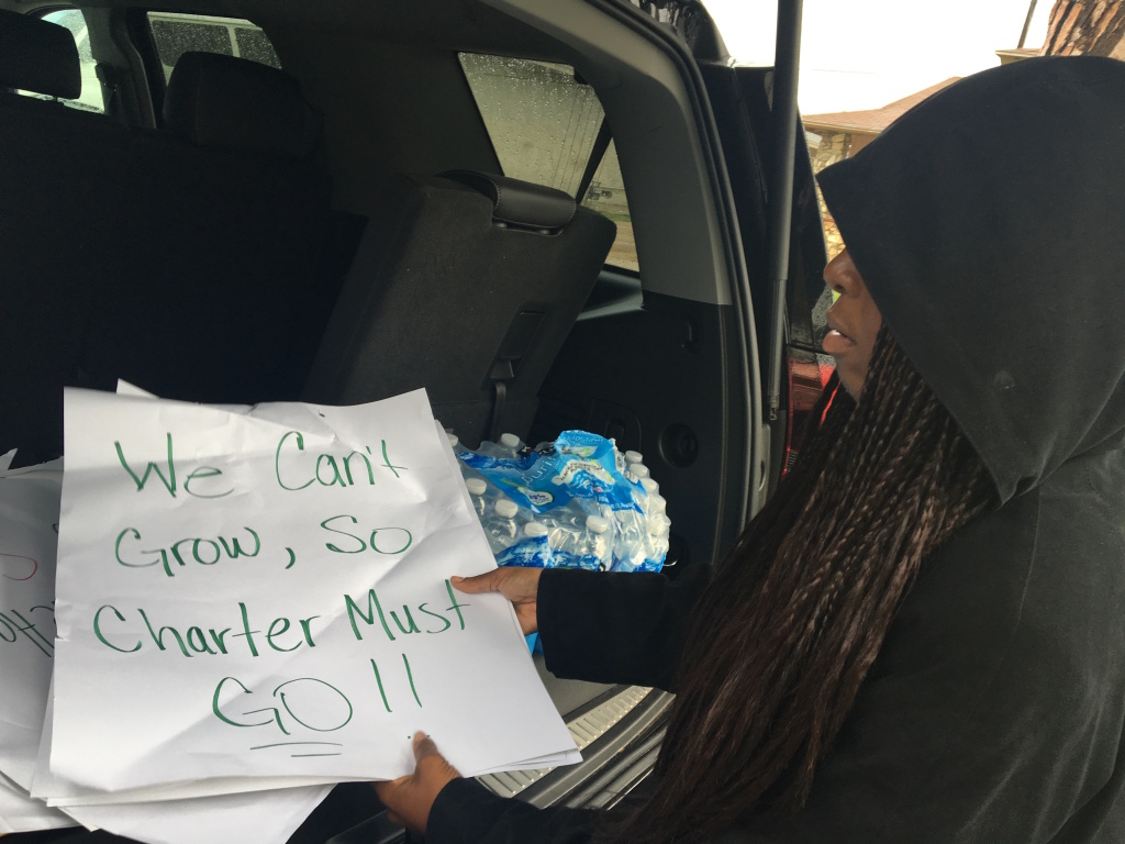 Maisha Riley, school leader at Community Preparatory Academy, a charter school, pulls from her trunk a stack of protest signs left along the fence of the L.A. Unified campus in Carson where they're co-located.
