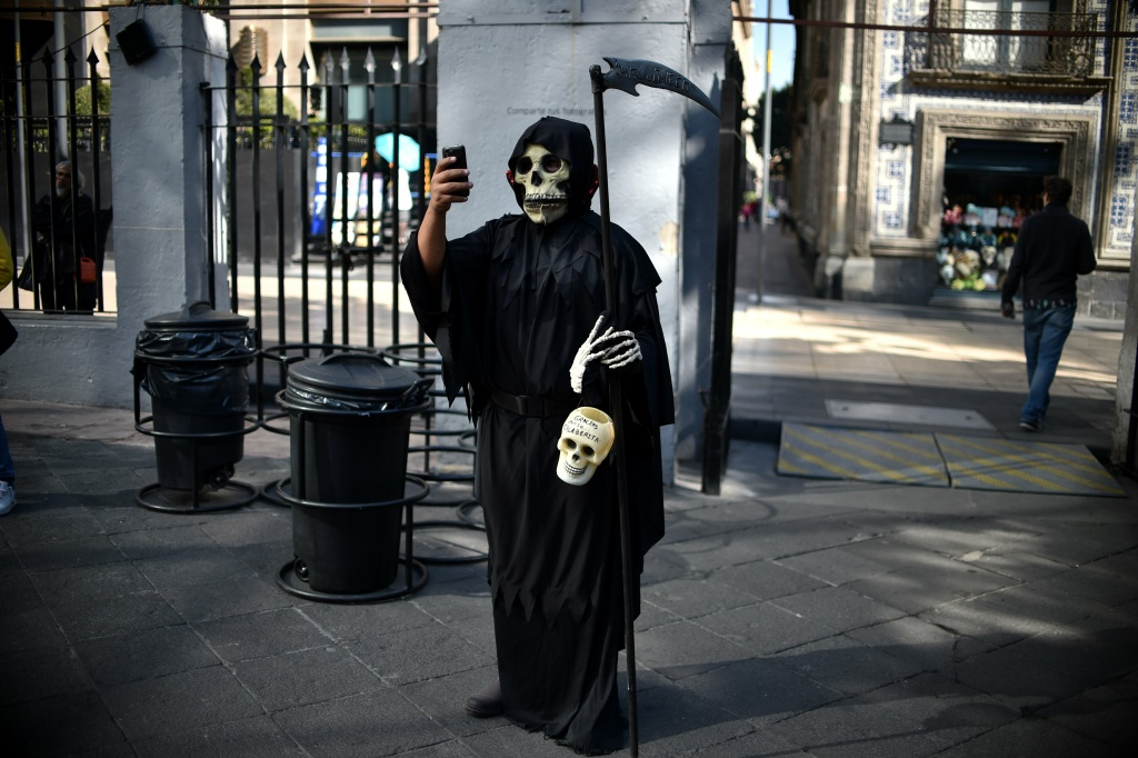 Death may not take a holiday but it does take a selfie. A man is dressed up for an exhibition of altars organized by the Historic Centre Foundation for Day of the Dead in Mexico City on November 1, 2016.