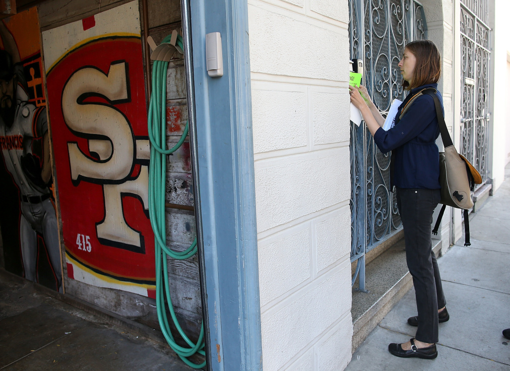A protestor with the San Francisco Tenant Union hangs a sign on a the exterior of a building during a demonstration outside of an apartment building that allegedly evicted all of the tenants to convert the units to AirBnb rentals