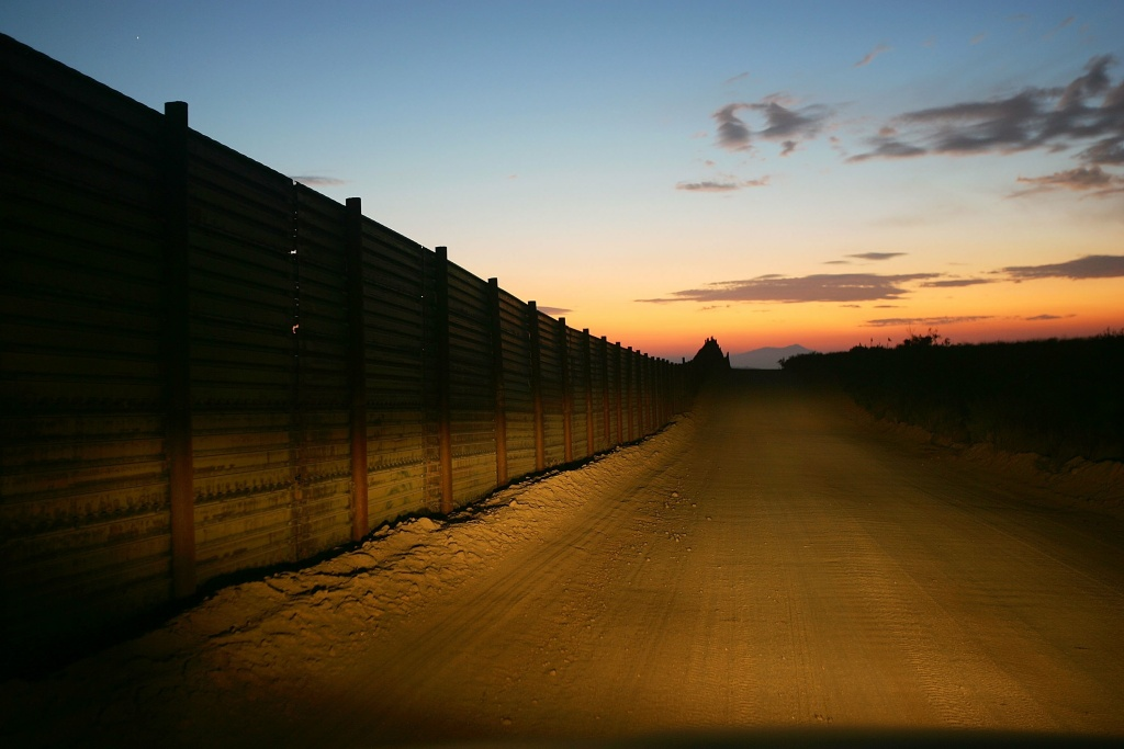 The US-Mexico border fence is illuminated by car headlights in an area where activists opposing illegal immigration search for border crossers on October 8, 2006 near Campo, California.