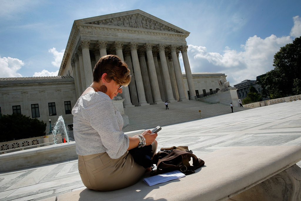 WASHINGTON, DC - JUNE 25:  Kirsten Luna from Holland, Michigan, uses her smartphone outside the U.S. Supreme Court after a major ruling on cell phone privacy by the court June 25, 2014 in Washington, DC. The Supreme Court issued a ruling requiring law enforcement officials to have a search warrant to search the cellphones of suspects they arrest.  (Photo by Win McNamee/Getty Images)
