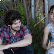 (Photo: Actress/comedian/songwriter Charlyne Yi spelling her favorite word with her hands. Left, Off-Ramp contributor Chris Greenspon. Credit: Sarah Jo Collins)