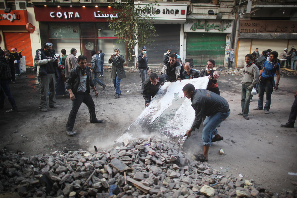 CAIRO, EGYPT - NOVEMBER 23:  Protestors clear debris from Mohammed Mahmoud Street after police withdrew on November 23, 2011 in Cairo, Egypt. Thousands of Egyptians are continuing to occupy Tahrir Square after four days of clashes with security forces despite a promise from military leaders to bring forward Presidential elections.  (Photo by Peter Macdiarmid/Getty Images)