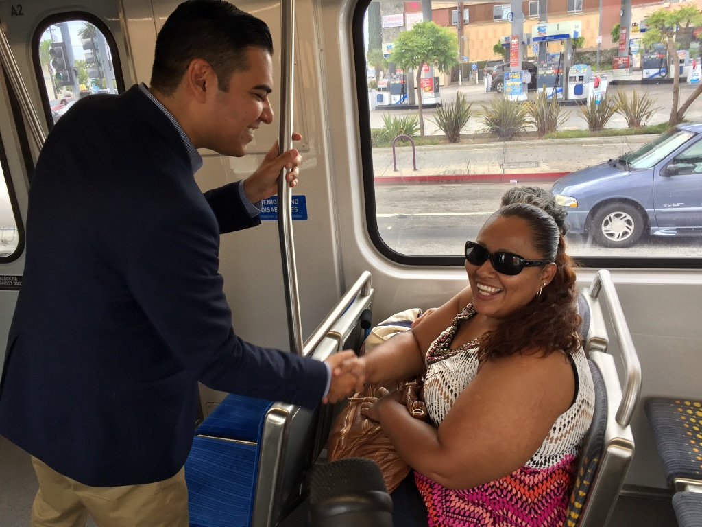 Long Beach Mayor Robert Garcia greets rider Rosa Guadalupe on a Blue Line train. Garcia, a Metro board member, wants to reverse declining ridership on the agency's oldest line. He has been gathering feedback from riders on visits to each of the line's 22 stations.