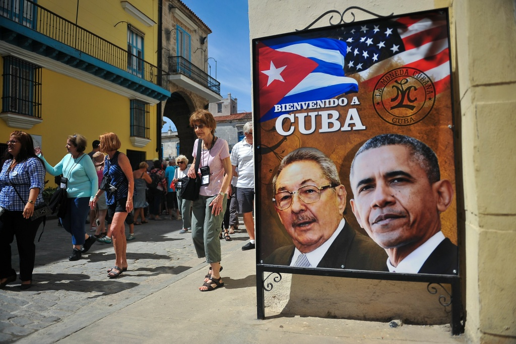 Tourists walk next to a poster of Cuban President Raul Castro and US president Barack Obama in Havana. The Obama Administration announced an end to the policy known as
