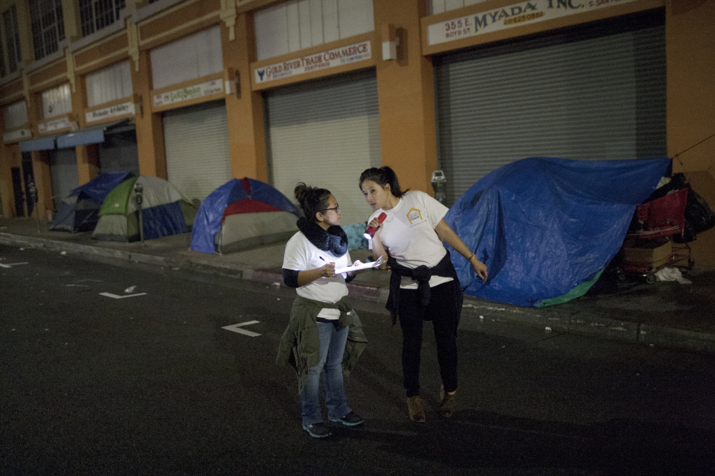 Volunteers count homeless people on a dark street on Skid Row during the 2015 Greater Los Angeles Homeless Count conducted by the Los Angeles Homeless Services Authority (LAHSA) on January 29, 2015 in Los Angeles, California.