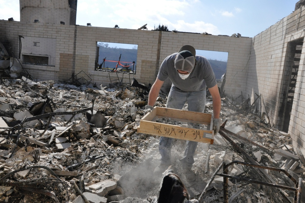 Gavin Floyd sifts through the wreckage of a dormitory destroyed in the Thomas Fire at the Ojai Valley School's Upper Campus on Dec. 20, 2017.