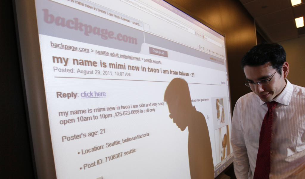 Washington state assistant attorney general Jonathan Mark walks past a display of a Backpage.com ad following a news conference about action being taken against the adult services site Wednesday, Aug. 31, 2011, in Seattle.