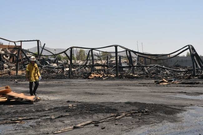 Firefighters sift through the rubble of a wooden pallet company in Fontana on Sunday, May 20, following a huge blaze which completely destroyed the property. The cause remains under investigation.