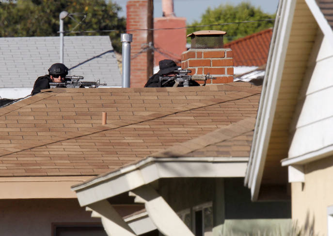 Inglewood police snipers take up a position outside a residence, Wednesday, Nov. 27, 2013, in Inglewood, where a police officer was shot and another received minor injuries in a confrontation with a gunman who barricaded himself inside a home and could be holding a hostage, authorities said.