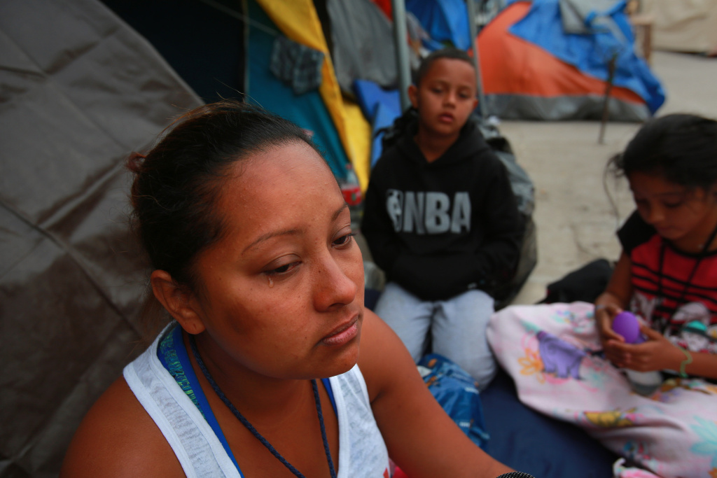At the El Barretal temporary migrant shelter in Tijuana, Abigail Thompson Maldonado from Honduras, talks about the journey she and her husband and their three children made to reach this spot on Dec. 16, 2018. In the background are Luis Antonio, 9, and Alexandra, 11.