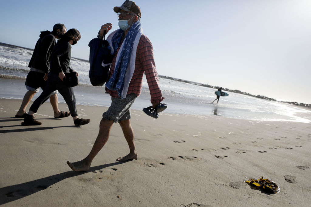 People wear face masks walking along Venice Beach on the day Los Angeles County reopened its beaches, which had been closed due the coronavirus pandemic, on May 13, 2020 in Venice, California.