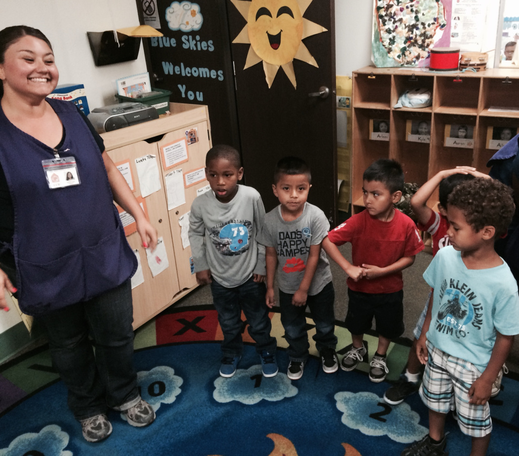Long Beach preschool teacher Anabel Lopez leads children in a round of singing and dancing. Lopez has a bachelor's degree and receives $11.75 an hour where she teaches at Comprehensive Child Development Center.