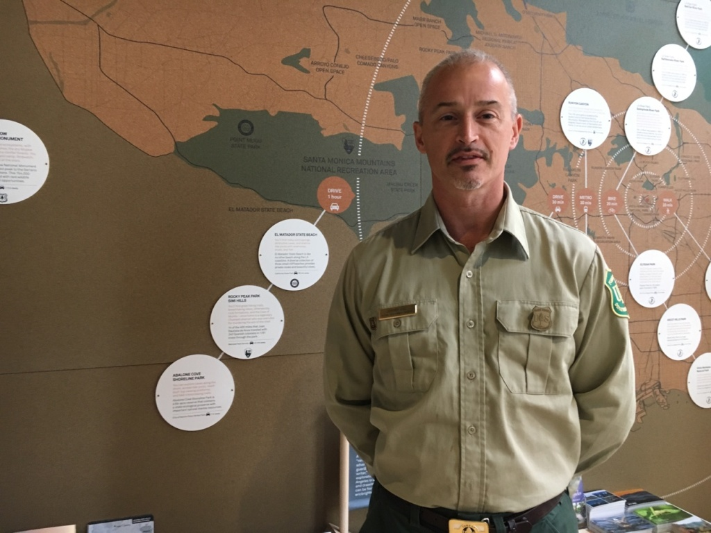 Jeff Vail, Forest Supervisor with the Angeles National Forest, next to a map that shows access to hiking and recreational areas near to urban L.A.
