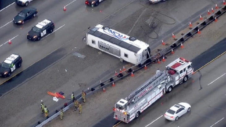 Firefighters help as a tour bus is towed out of a drainage ditch after the bus went off the shoulder of an Interstate 10 off-ramp in Baldwin Park, Calif. on Monday Dec. 23, 2013. The tour bus heading back from a Southern California casino crashed on a freeway east of Los Angeles early Monday, injuring 13 people, authorities said.