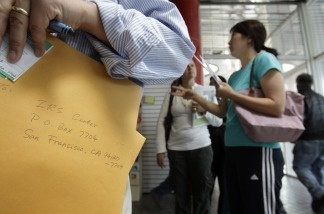 A man waits in a long line to turn in his federal and state tax forms on April 18, 2011, at a U.S. Post Office in San Jose.