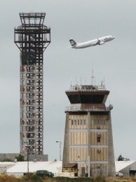 An Alaska Airlines plane takes off past a half-completed 236-foot FAA control tower (L) at Oakland International Airport on July 26, 2011 in Oakland, California. Construction crews working on a new FAA air traffic control tower at Oakland International Airport were told last Friday to stop working after the U.S. House of Representatives refused to reauthorize routine funding of the FAA, resulting in 4,000 FAA employees being furloughed and nearly $2.5 billion in airport construction jobs being halted.