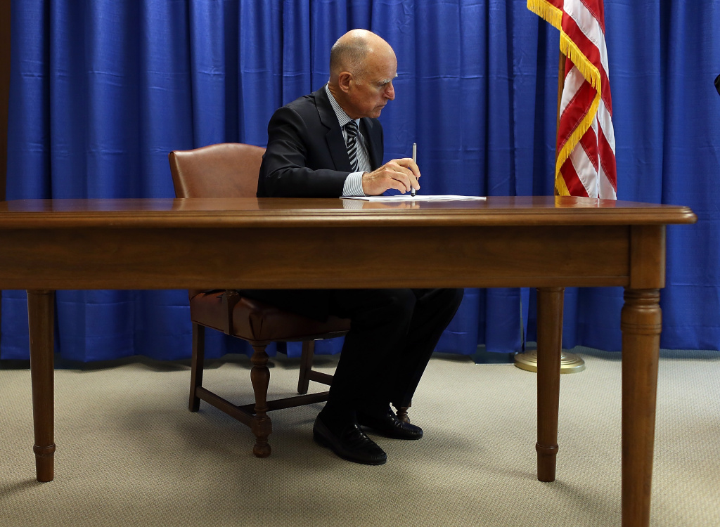 File: California Governor Jerry Brown prepares to sign copies of the California Homeowner Bill of Rights (AB 278 and SB 900) on July 11, 2012 in San Francisco, California.