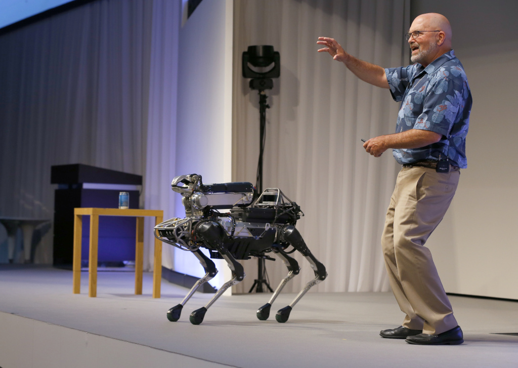 In this July 20, 2017 file photo, Boston Dynamics Chief Executive Marc Raibert speaks about his four-legged robot SpotMini during a SoftBank World presentation at a hotel in Tokyo. The robotics company known for its widely shared YouTube videos of nimble, legged robots opening doors or walking through rough terrain is finally preparing to sell some of them after years of research.
