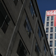 "A large ""rent"" banner is posted on the side of an apartment building in San Francisco, California."