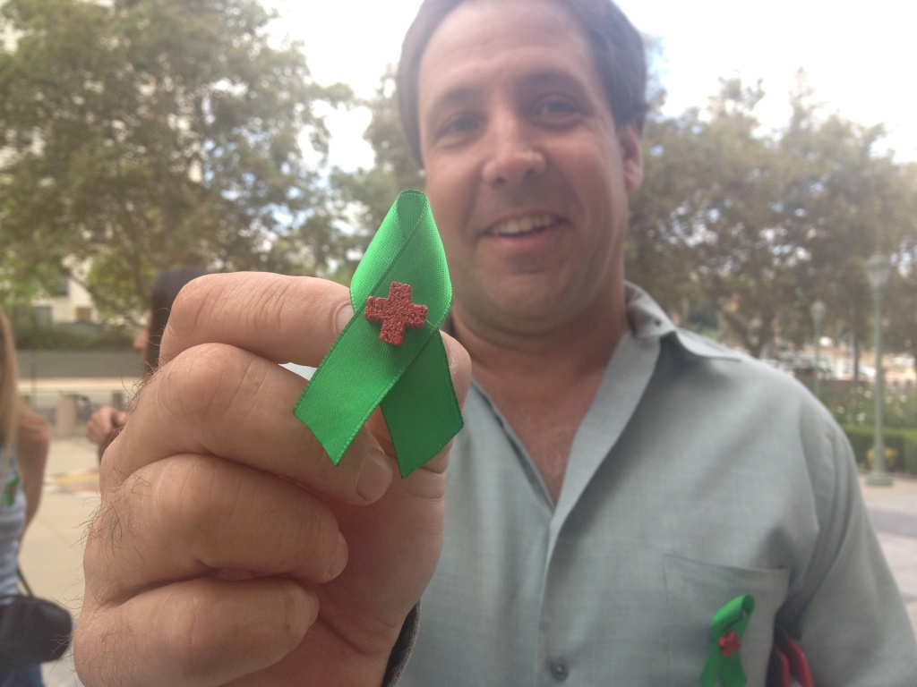 Joe Grumbine, who also faces marijuana charges in state court for operating dispensaries, holds up a green ribbon lapel pin worn by several supporters who attended Aaron Sandusky's federal trial hearing Tuesday.