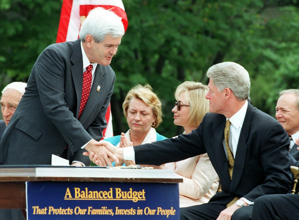 US Speaker of the House Newt Gingrich (L), R-GA, shakes hands with US President Bill Clinton (R), as First Lady Hillary Clinton (2nd-R) and US Representative Barbara Kennelly (C), D-CT, watches before the President signed the Balanced Budget Agreement on the South Lawn of the White House 05 August in Washington.