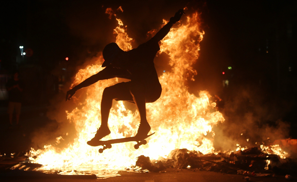 A young man practices a skateboarding move in front of a fire set by protestors on March 15, 2017 in Rio de Janeiro, Brazil.
