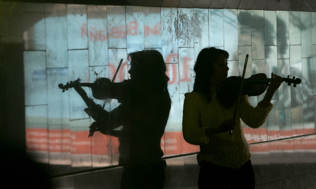 A street musician is reflected in a marble wall as she plays violin in a pedestrian subway in the center of Kiev 11 October, 2007. AFP PHOTO/ Sergei SUPINSKY (Photo credit should read SERGEI SUPINSKY/AFP/Getty Images)