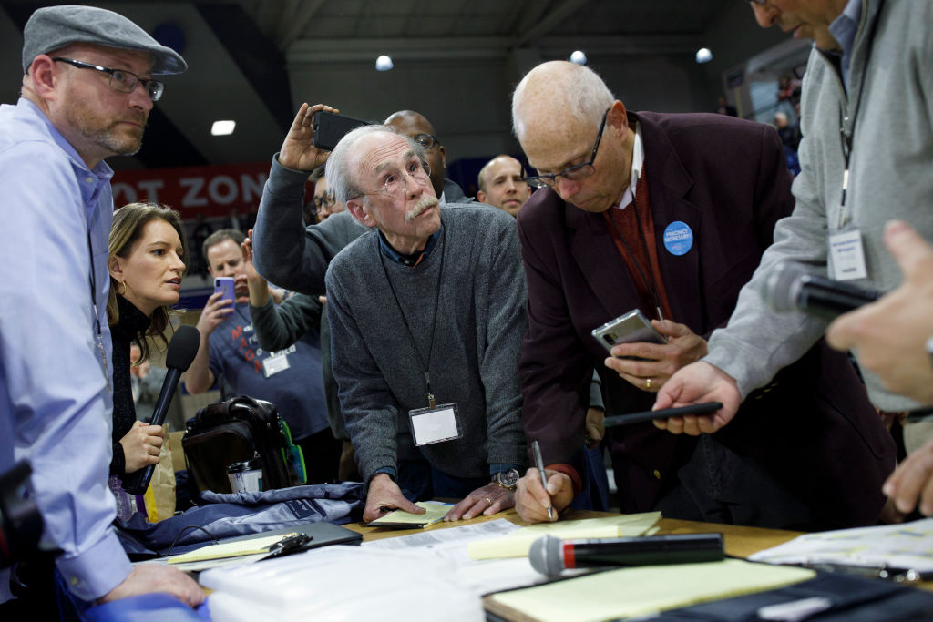 Officials from the 68th caucus precinct overlook the results of the first referendum count during a caucus event on February 3, 2020 at Drake University in Des Moines, Iowa, United States.