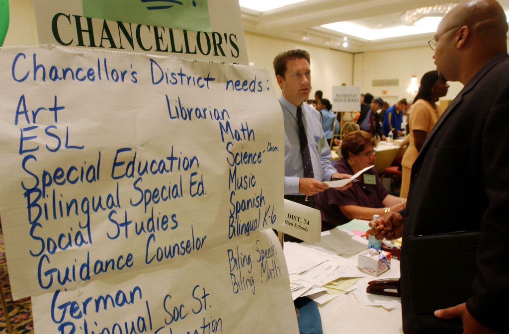 A teaching candidate speaks with a recruiter at a teachers job fair.