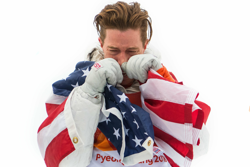 U.S. snowboarder Shaun White wraps himself in the U.S. flag after winning gold in the men's halfpipe. He was later criticized for dragging a flag on the ground at the 2018 Pyeongchang Winter Olympics.