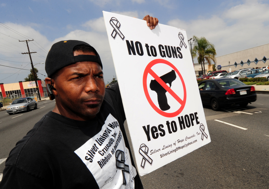 Gang interventionist Everett Bell, hands out peace message ribbons to passing motorists at the South Central Los Angeles location of the death of junior football star Dannie Farber Jr. who was mistaken for a rival gang member in Compton, California on May 28, 2011.