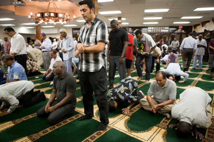 A man reads the Quran before Friday prayer at the Islamic Center of Southern California.