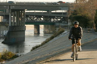 A bicyclist rides along a path running along the cement-lined Los Angeles River in Los Angeles.