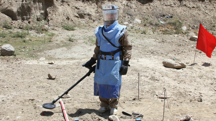 A de-mining expert demonstrates how to find land mines in a training area near Hakim Village in southeastern Afghanistan, where Soviet mines dating to the 1980s are still a danger.